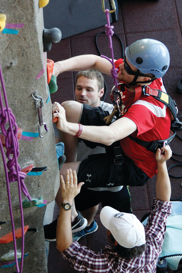 Nate Redman, in red, makes his way up the Parker Fieldhouse climbing wall as his occupational therapist Jeff Galloway, wearing a hat, and his friend Aaron Peterson, help him get started. Peterson, a friend of Redman's since their teen years, moved in with the Redman family to assist in Nate's care.