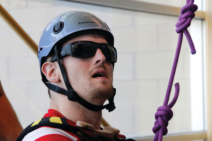 Nate Redman plans his ascent at the adaptive climbing wall at the Parker Fieldhouse. Redman has a rare genetic degenerative disorder and uses the wall to maintain his level of activity, improve his coordination and have fun.