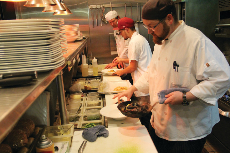 Cory Matthews, executive chef at West 29th Restaurant and Bar in Wheat Ridge, holds a pan of food in the kitchen at dinner time Aug. 8. In the back, Chris Johnson, 56, an ACFCCA apprentice, stands ready to assist.
