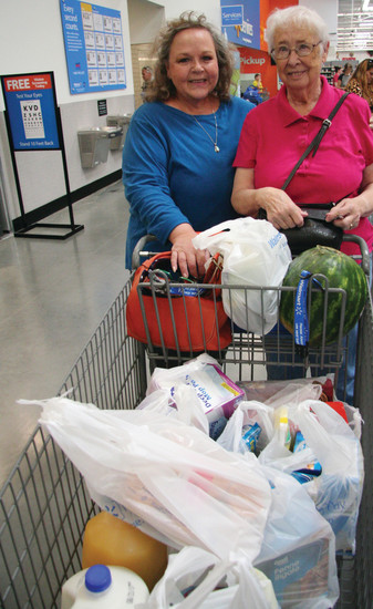 "Mary Murphy helps her mother Joan Murphy, roll their shopping cart out the front door of the new Arvada Walmart on opening day. ""We just wanted to see it finally open,"" said Mary Murphy. ""They closed my other Walmart, that I'm not happy about,"" said Joan, 87, when asked why she was shopping at the new store."
