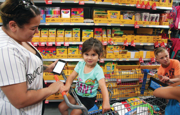 "Alexis Vigil, left, shops for school supplies with her three children. With two 9-year-olds to shop for, the list of supplies is long. ""It's just easy here, becuase they just opened, so nothing's out of stock,"" she said."