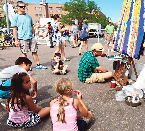 A group of young people circle around Golden artist Jesse Crock as he live paints during the Golden Fine Arts Festival last year. Crock will do live painting again this year at the festival, which takes place Aug. 19 and 20 in historic downtown Golden.