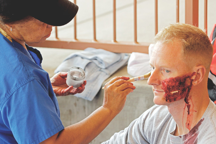 Bryan Muscutt, a firefighter from West Metro Fire Rescue district, holds still as Deidre McGee, coordinator of surgery simulation at Rocky Vista University, applies the finishing touches to his makeup. Muscutt volunteered to portray a bombing victim for a training exercise between the FBI, the Douglas, Jefferson and Arapahoe County Sheriffs' Departments, South Metro Fire Rescue, the Cunningham and Franktown Fire Protection Districts, and bomb squads from the sheriffs offices.