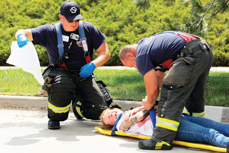 Emergency Medical Technicians treat volunteer actor Morgan Stanley during a simulated explosion training exercise. Stanley and many other volunteers are second-year students at nearby medical school Rocky Vista University.