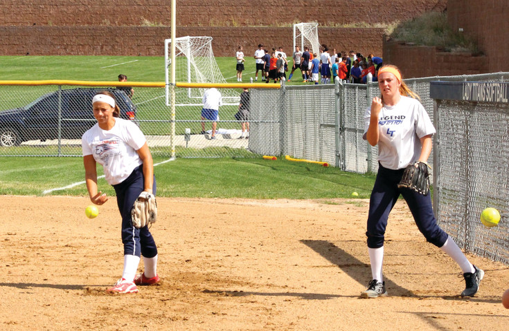 Legend pitchers Zoey LeCompte (left) and Bella Mumford warm up during a preseason Titans' summer camp workout.