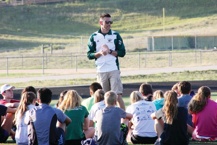 Mountain Vista cross country coach Jonathan Dalby talks to his varsity team prior to a recent early morning workout.