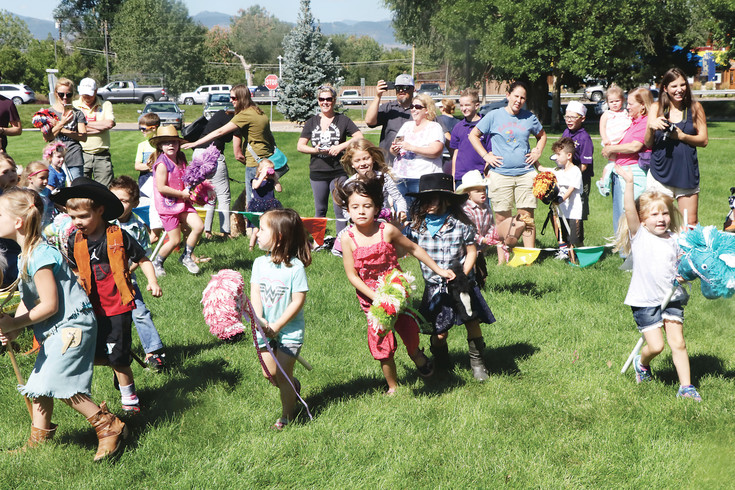 Enthusiastic 4- to 6-year-old riders gallop around the course during their age group's turn to take part in Bruce Wolf Stick Horse Stampede. About 100 toddlers to 12-year-olds took part in the stampede that was held on the Arapahoe Community College campus and was among the Aug. 13 Western Welcome Week events.