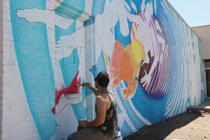 Muralist Bobby MaGee Lopez works on his mural for the third annual MuralFest on Aug. 12. His objective for the mural is to blend his own vision with the goals of 40 West Arts.