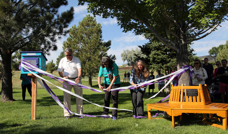 Peter Van Arsdale, Celia Van Arsdale Powell and Elise Van Arsdale cut the ribbon on a Little Free Library and Wrap Around Bench that were dedicated Aug. 17 in honor of their parents, Wayne and Mardie Van Arsdale, whom the school is named after.
