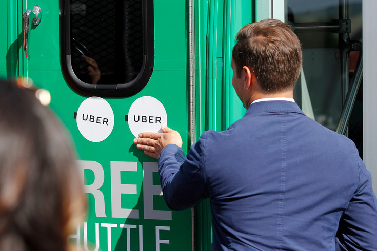 Uber Denver Senior Operating Manager Joe Sanfilippo brands a Link shuttle with the Uber logo during a ceremony debuting the Link on Demand service. Sanfilippo says the program could be extended to include buses exclusively for riders using wheelchairs or other specialty services. Photo By Tom Skelley.