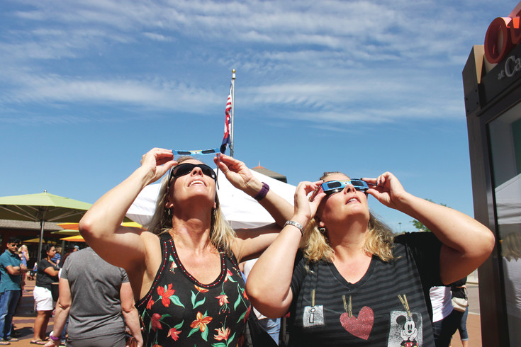 Ann Nelson and Donna Orr, both of Castle Rock, watch during the solar eclipse on Aug. 21 at the Outlets at Castle Rock.
