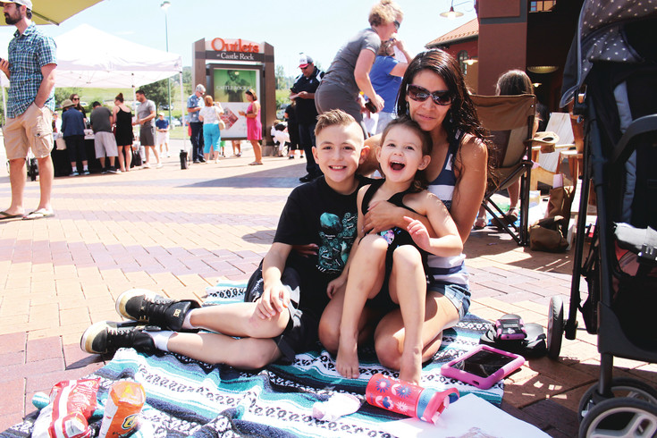 Michele Andersen, of Highlands Ranch, sits with 10-year-old Alani and 4-year-old Kiana in the courtyard at the Outlets at Castle Rock on Aug. 21 for a solar eclipse viewing party. Although the family wasn't able to acquire eclipse glasses, they said many people at the event shared glasses with them.