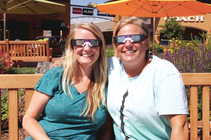 Adie, of Colorado Springs, and Amber Loberg try out their solar eclipse glasses ahead of the peak viewing time on Aug. 21.