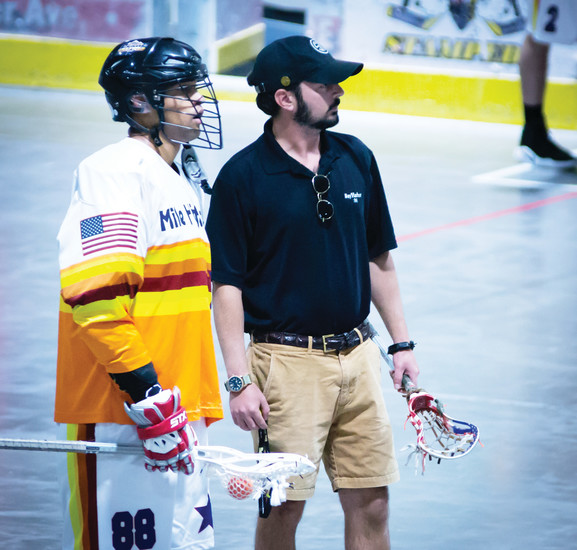 Arthur Kleinpell, the Mile High Stars assistant coach, with one of the team's lacrosse players at one of the team's games. The Stars are based in Lakewood, and compete in the Colorado Regional Box Lacrosse League.