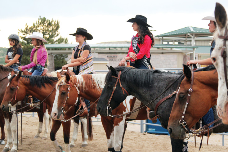 Candidates for rodeo queen and princess line up to hear feedback from instructors at a horsemanship practice event in July.