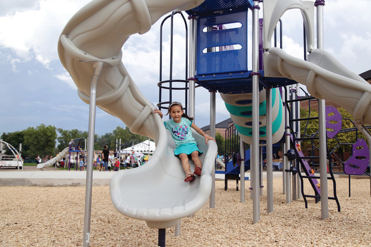 Gina Jones, first grade, tests on a slide on the new playground at Lawrence. A goal was to add more slides for play.