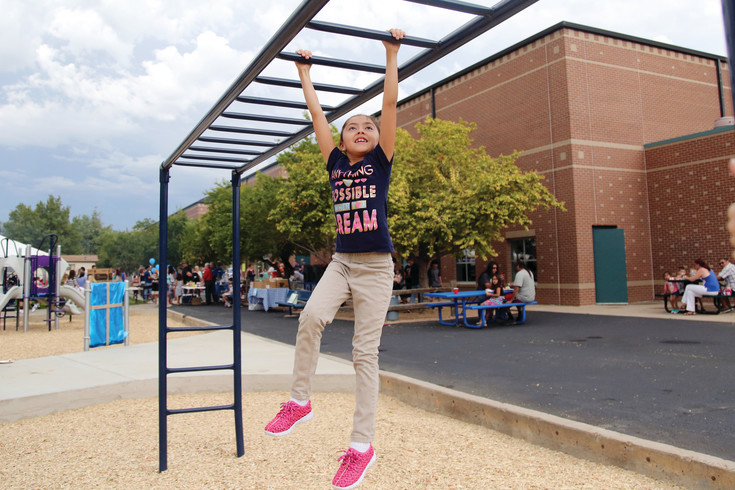 Elionna Garaz, 6, tests out the monkey bars at the new Lawrence Elementary playground Aug. 15.