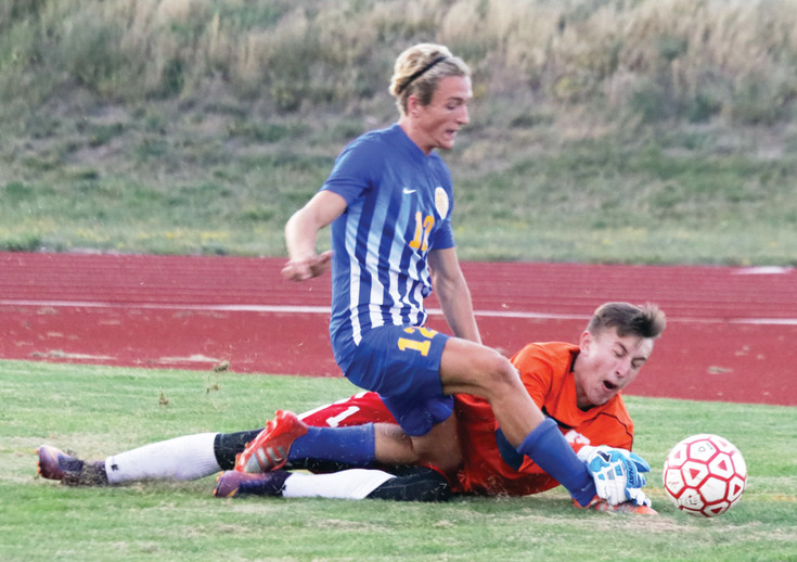 Elizabeth goalie Dylan Handlovitch dives to win the battle with Wheat Ridge player Ian Spetnagel during the Aug. 24 non-league soccer game. Handlovitch won the battle for the ball but Spetnagel later scored the winning goal as the Farmers won 4-3 in overtime.