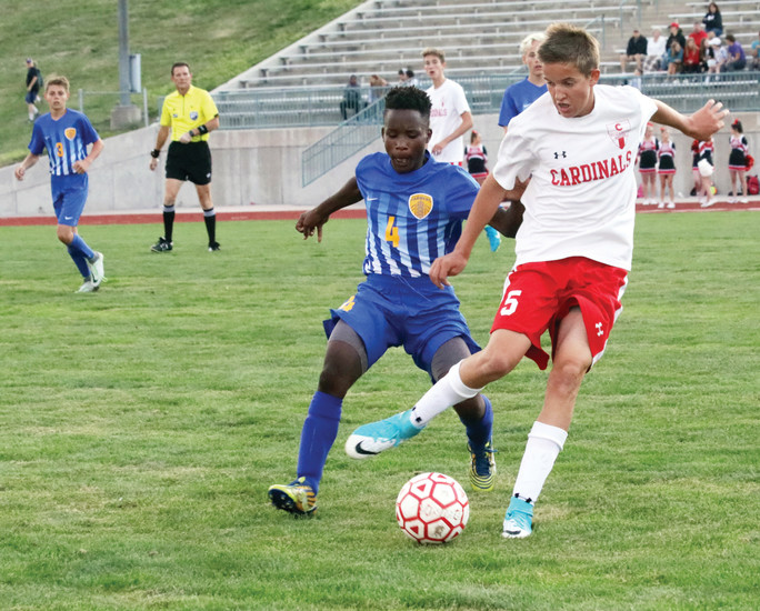 Cardinal midfielder DJ McCliesh prepares to kick the ball before Wheat Ridge forward Jean Baptiste can get to it during the Aug. 24 non-league soccer game played at Elizabeth High School. McCliesh got the ball away but Wheat Ridge won the game 4-3 in overtime.