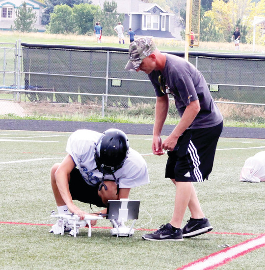 Highlands Ranch assistant coach Brian Krzeminski, right, who owns the drone, asked Jeremy Henning to operate it, given that kickers are usually idle during most of the practice sessions.