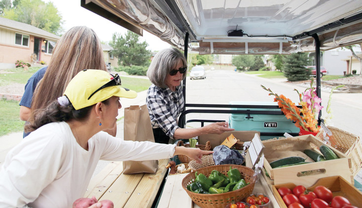 Shelley Cook distributes fresh produce from the Arvada Veggie Van during her Wednesday evening route in the Memorial Park neighborhood.