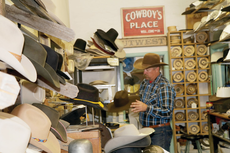 The wall on the left is a display showing some of the hats Brook Briddle has made in the 14 years he has owned and operated the Powder River hat shop in Elizabeth. Briddle begins with a beaver fur felt body to create a Western hat made specifically for its new owner.