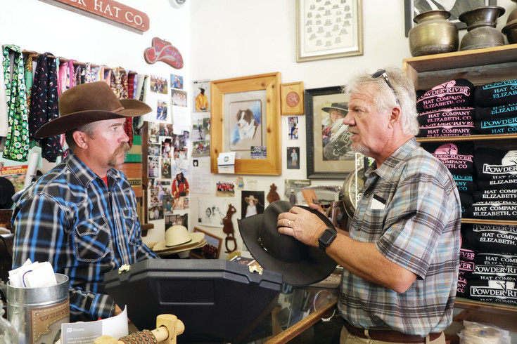 Longtime customer Tim Brantley, right, compliments Elizabeth hatmaker Brook Briddle on the complete custom work done on the black hat he is holding. Brantley said Briddle is the only one who can do work for him and has been a customer for more than 10 years.