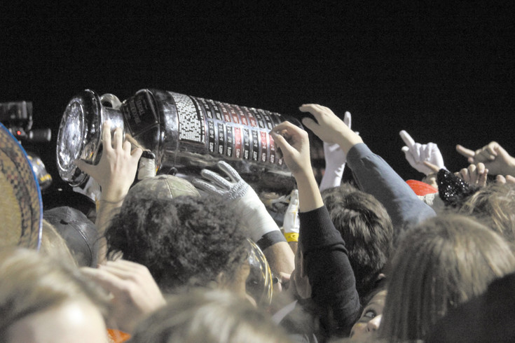 Players and fans hold the Brookridge Trophy high after Arapahoe won the 2015 football game with Heritage. The winner of the rivalry game gets to keep the trophy until the next Arapahoe-Heritage game decides which school becomes keeper of the milk can for a year.