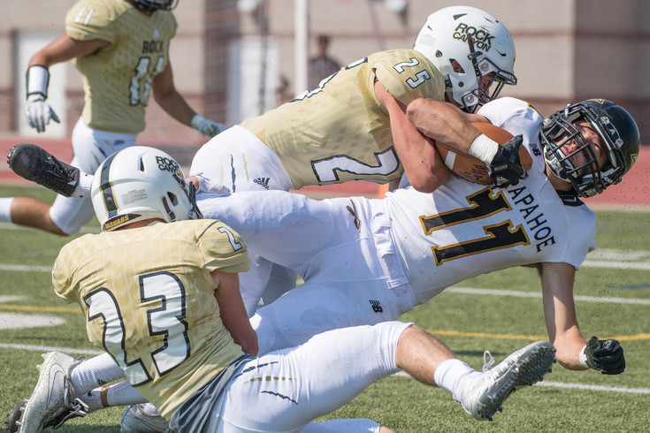 Rock Canyon's Bryce Henningsen and Zach Wilson (23) pull Arapahoe's Jack Hollingsworth to the ground.  The Jaguars started off the season with a 38-7 victory over the Warriors at Echo Park Stadium on Sept. 2.