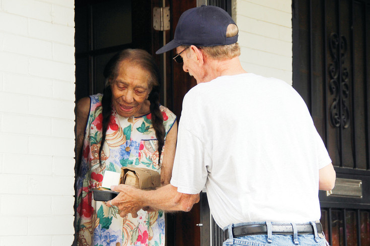 "Wayne Chitwood, who's been delivering food with Meals on Wheels for about 8 years, brings Lometa Gaskin her daily serving of lunch and conversation on Aug. 11. Chitwood says most clients don't have any social interaction beyond the daily deliveries. ""They're always very appreciative,"" he says. ""That's why I'm doing it."""