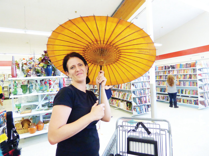 Jennifer Jennings strikes a pose with her newfound parasol. She used to frequent the old Savers store, and was thrilled to find the new Arc up and running.
