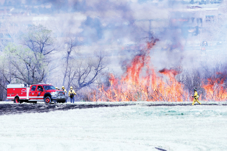 South Metro Fire Rescue personnel monitor a brush fire along the east side of the Cherry Creek Trail on April 13. Crews from Franktown and Cunningham Fire Protective Districts assisted SMFR in fighting the blaze, driven by high winds and fueled by abundant dry vegetation.