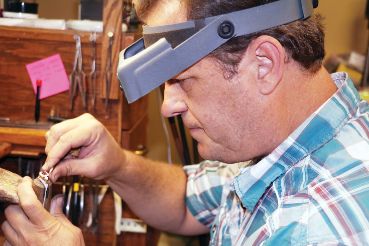 Tim Brown makes adjustments to the stone setting on a ring he is creating for a customer. Brown and his wife Renee own and operate their store in the Safeway Center in Elizabeth where they do watch battery replacements, jewelry repairs and create custom jewelry items for their customers.