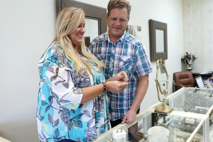 Renee Brown and her husband Tim hold one of their custom-made items they created and have for sale in their jewelry shop located in the Safeway Center in Elizabeth. The couple is celebrating their fourth anniversary at the location this month.