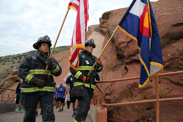 West Metro firefighters Chris Trost and Tyler Hecox lead the pack up the south ramp at Red Rocks Amphitheater carrying the American and Colorado flags.