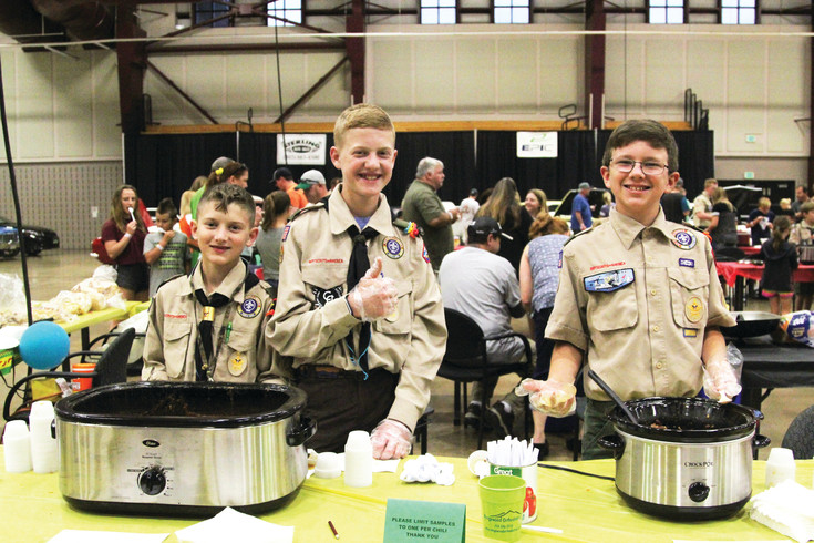 Camden Dorris, next to his brother Cody, and Richard Dixon give a thumbs up while serving their homemade chili at the 6th Annual Chilifest on Sept. 9.
