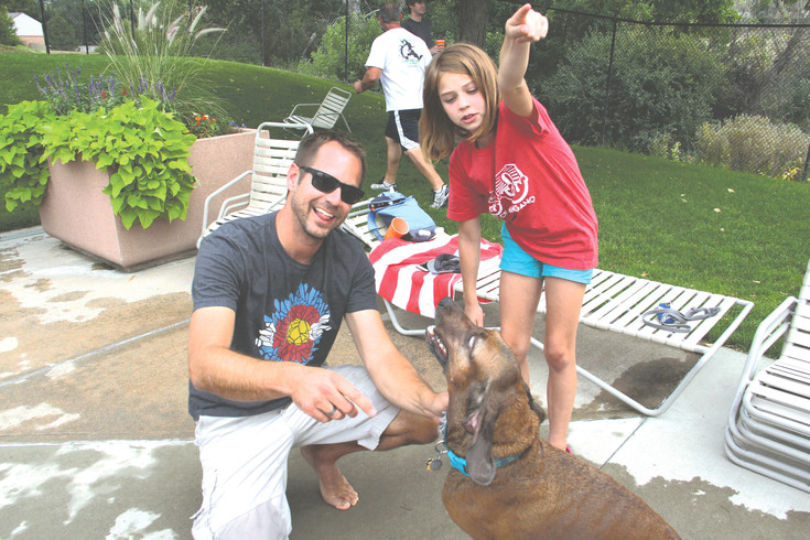 "Jeff Ames, 45, and daughter Raina Ames, 9, pose with Auggie, their 5-year-old dog, at the Yappy Hour event Sept. 9. Ames' three children have all been on the swim team at Holly Pool, and the swim coach, a dog-lover, ""made sure we knew about the event,"" Ames said. They've been coming for a few years."
