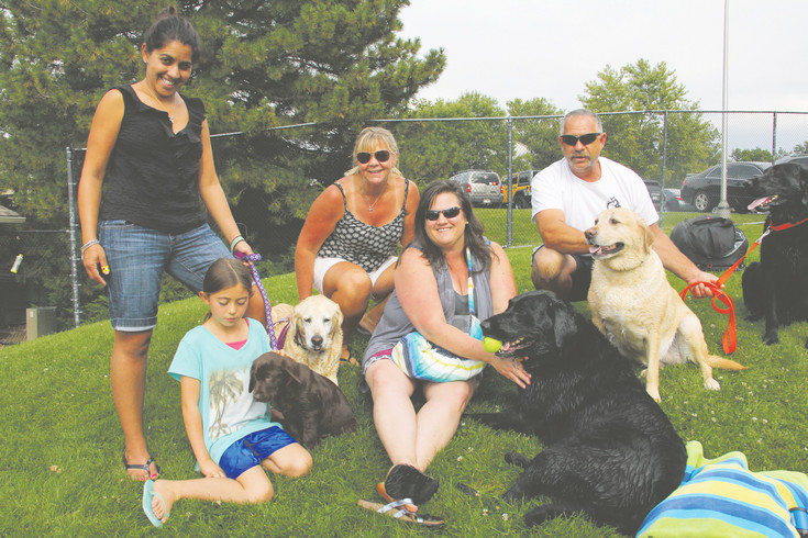 "Left to right: Shauna Bevirt Allison Bevirt, Mimi Macmaster, Amy Ordonio and Rod Macmaster with dogs Tracy (11 weeks old), Rubie (13 years), Shamrock (6), Callie (6) and Jake (6) on Sept. 9. Ordonio is the sister-in-law to the Macmasters, and the Bevirts are her neighbors. Ordonio and the Macmasters own the five dogs, and Ordonio got Tracy two weeks ago — ""I decided we needed a little chocolate in the mix,"" she said. The other dogs have been coming to Yappy Hour for about five years, and they all burst with excitement when they see where they're going through the car windows. ""The older one, even though she can't jump in, she loves to walk (around) and watch everyone. So everyone's happy,"" said Ordonio, 45, who has been coming to Holly Pool since age 2."