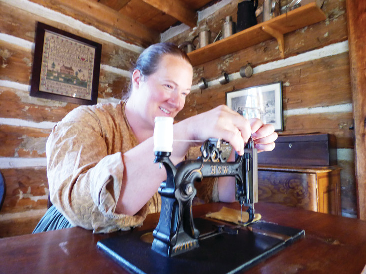 Andrea Wilhelm threads a period sewing machine, which would have been a rare and expensive item for a pioneer homestead.