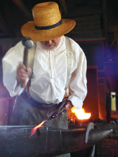 Blacksmith Steve Loo pounds out decorative ironwork at the Littleton Museum.