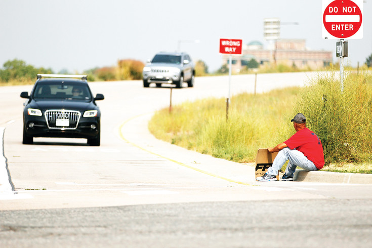A pandhandler rests at the corner of Yosemite St. and the C-470 offramp, near the Park Meadows mall on Sept. 7. Lone Tree Patrol Sgt. Scott Cavenah says there may be between six and 14 panhandlers in the city on warm weather days.