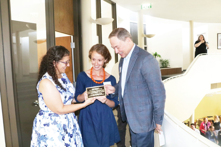 Judy Riley, right, Erika Warzel and G. Timothy Laney hold the plaque stating the Englewood Community Bank of Colorado that was designed by Charles Deaton has been added to the National and Colorado   Registry of Historic Places. Riley is the Englewood bank manager, Warzel is History Colorado's national and state register historian and Laney is president and CEO of National Bank Holding. Plans are to place the plaque in the main entrance foyer. Photo by Tom Munds