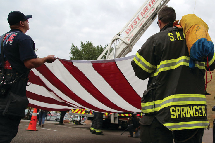 Members of West Metro and South Metro Fire came together to raise the American flag for the opening ceremony at the Colorado 9/11 Stair Climb.