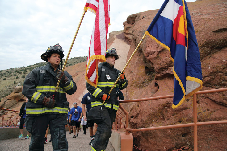 West Metro firefighters Chris Trost and Tyler Hecox lead the pack up the south ramp at Red Rocks Amphitheatre carrying the American and Colorado flags.