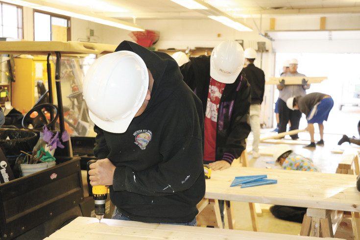 Students in Wheat Ridge High School's shop classes last December help to build the benches that were given to local elementary schools for decoration, and then auctioned off during this year's Carnation Festival.