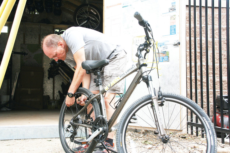 Craig Berkley, assistant bike librarian at the Golden Bike Library, checks the tire pressure on one of the bike library's adult bikes in the fleet. This is the second year the bike library has been opened, and the popularity of it has increased by about 600 riders over last year.