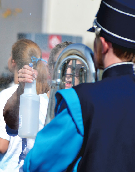 Amy Yankovich helps hydrate a Ralston Valley High School band member. Parents of band students sprayed them with water and provided water to sip as they marched through the Arvada Harvest Festival parade on Saturday, Sept. 9.