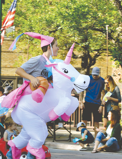 Jaden Heese, 11, goes through the Arvada Harvest Festival parade like he's riding a unicorn. Jaden was in the parade representing Hackberry Hill Elementary School.