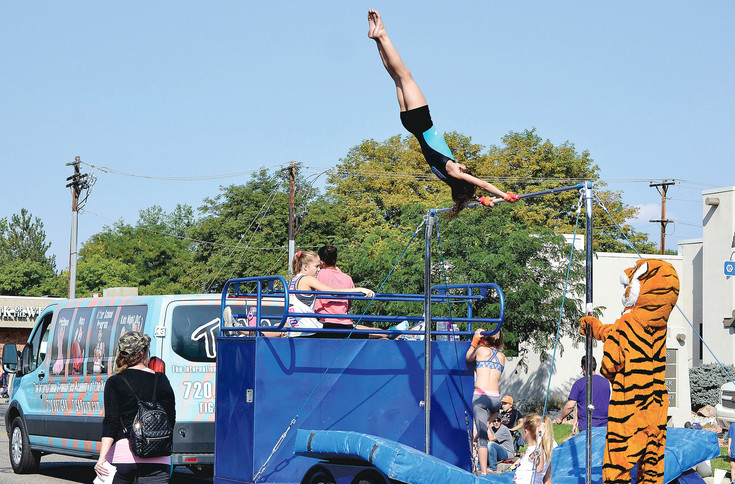 Quincey McCoy, 10, does flips on a bar with Tigar Gymnastics during the Harvest Fest parade Sept. 9.