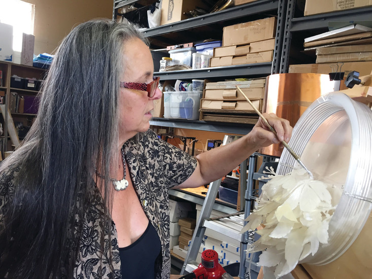 Judy Gardner creates a new art piece with 3-D printed florals in her Arvada studio.